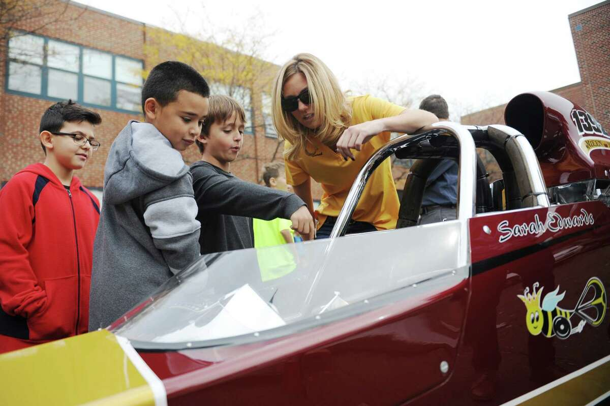 NHRA drag racer Sarah Edwards shows the controls of her top dragster vehicle to fourth-graders Youssef Taoyfik, left, Allan Medina, center, and Steven Lopez at Julia A. Stark Elementary School. Edwards, a Stark School alumna and Stamford native, talked about her racing career and the science and aerodynamics of racing to a group of fourth-grade science students before letting the students get a close up look at her 1100 horsepower vehicle.
