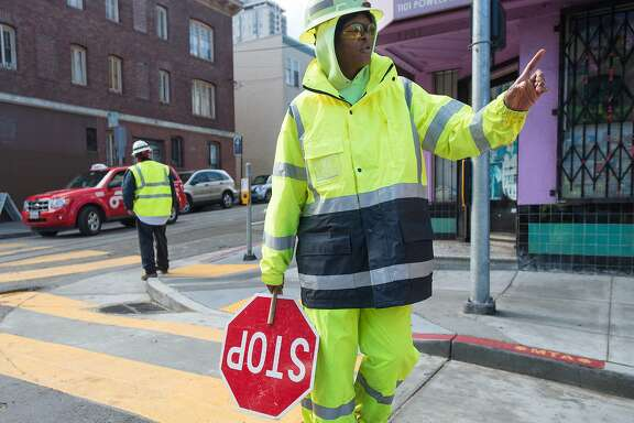 A crossing guard wears a rain suit while directing traffic after a rain storm in San Francisco on November 02, 2015.