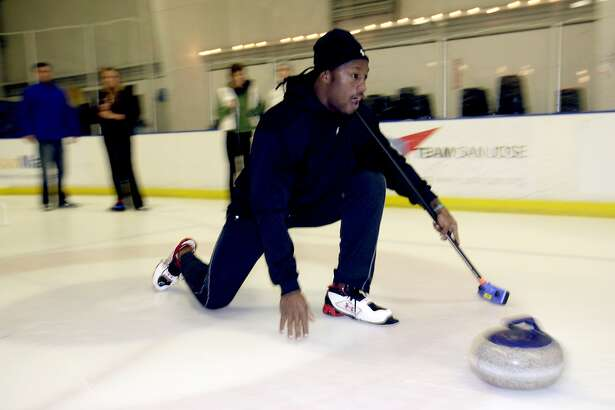 In this Nov. 3, 2009, file photo, San Francisco 49ers football player Vernon Davis learns the game of curling with members of the San Francisco Bay Area Curling Club, in San Jose. Davis is headed to his first Pro Bowl and his first Olympics, too. The 49ers tight end will be an honorary captain for the U.S. men's curling team next month at the Vancouver Olympics.