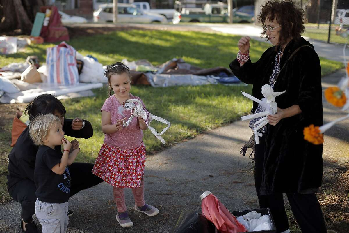 Maica Folch, right, shows skeleton adornments for her family altar to Jackson Renaudin, 3, and Zoe Renaudin, 5, and Carolina Aredalo during a Day of the Dead celebration at Garfield Square in San Francisco, Calif., on Monday, November 2, 2015.
