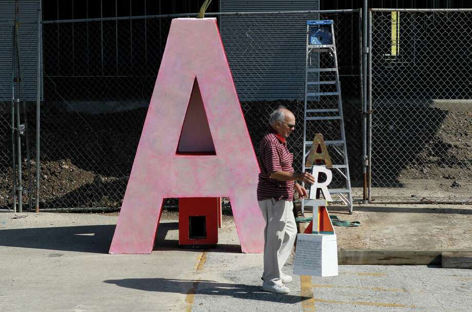 """David Adickes carries a miniature sculpture as workers install his large  """"ART"""" piece in front of the Silos at Sawyer Yards.>>Keep clicking for a look inside the Adickes Art Foundation Museum Photo: Steve Gonzales, Houston Chronicle / © 2015 Houston Chronicle"""