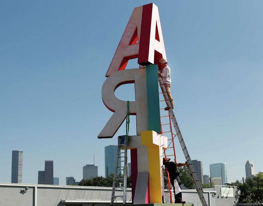 "Mike Scranton (top) prepares to weld the large ""A"" on Artists' David Adickes large  ""ART"" sculpture in front of the Silos at Sawyer Yards, 1502 Sawyer at Taylor. Antonio Vera assists in holding the ladder. Photo: Steve Gonzales, Houston Chronicle / © 2015 Houston Chronicle"