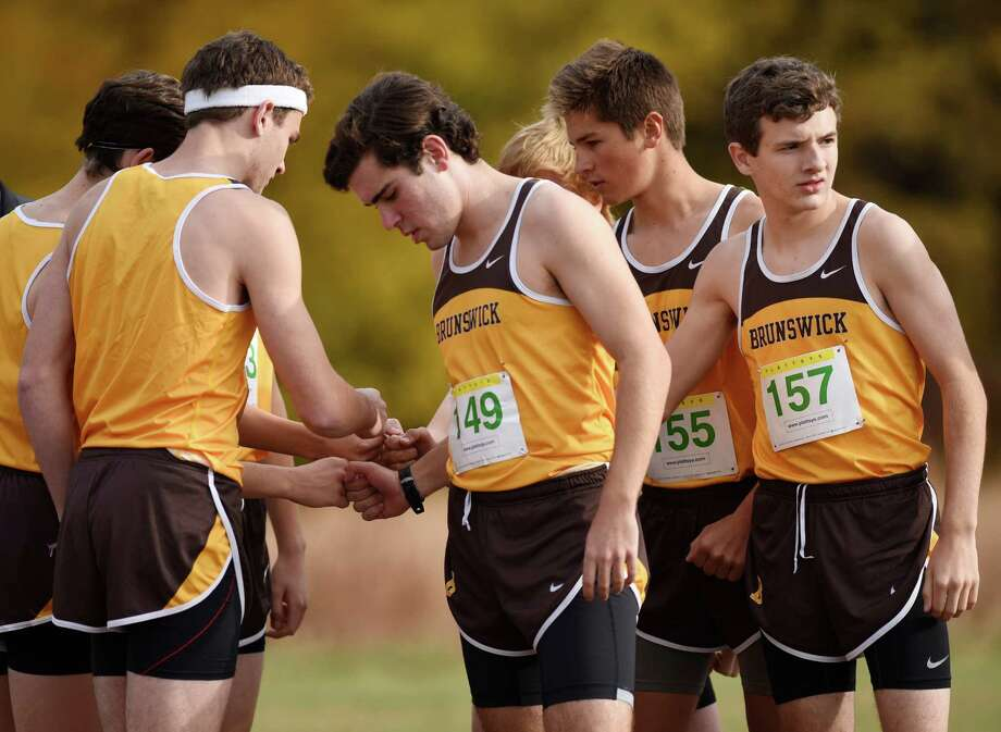 Brunswick cross country runners, including Andrew Israel (149), Jack Parkin (155) and Wesley Peisch (157), huddle before their race at the Fairchester Athletic Association (FAA) high school cross country championships at Waveny Park in New Canaan, Conn. Monday, Nov. 2, 2015.  Brunswick School won the boys team championship and School of the Holy Child won the girls team championship. Photo: Tyler Sizemore / Hearst Connecticut Media / Greenwich Time