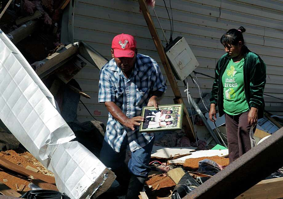 Ismael Tellez and his sister-in-law Rosa Tellez try to salvage items from his parents' manufactured home in Alvin that was damaged in the storm. Photo: James Nielsen, Staff / © 2015  Houston Chronicle