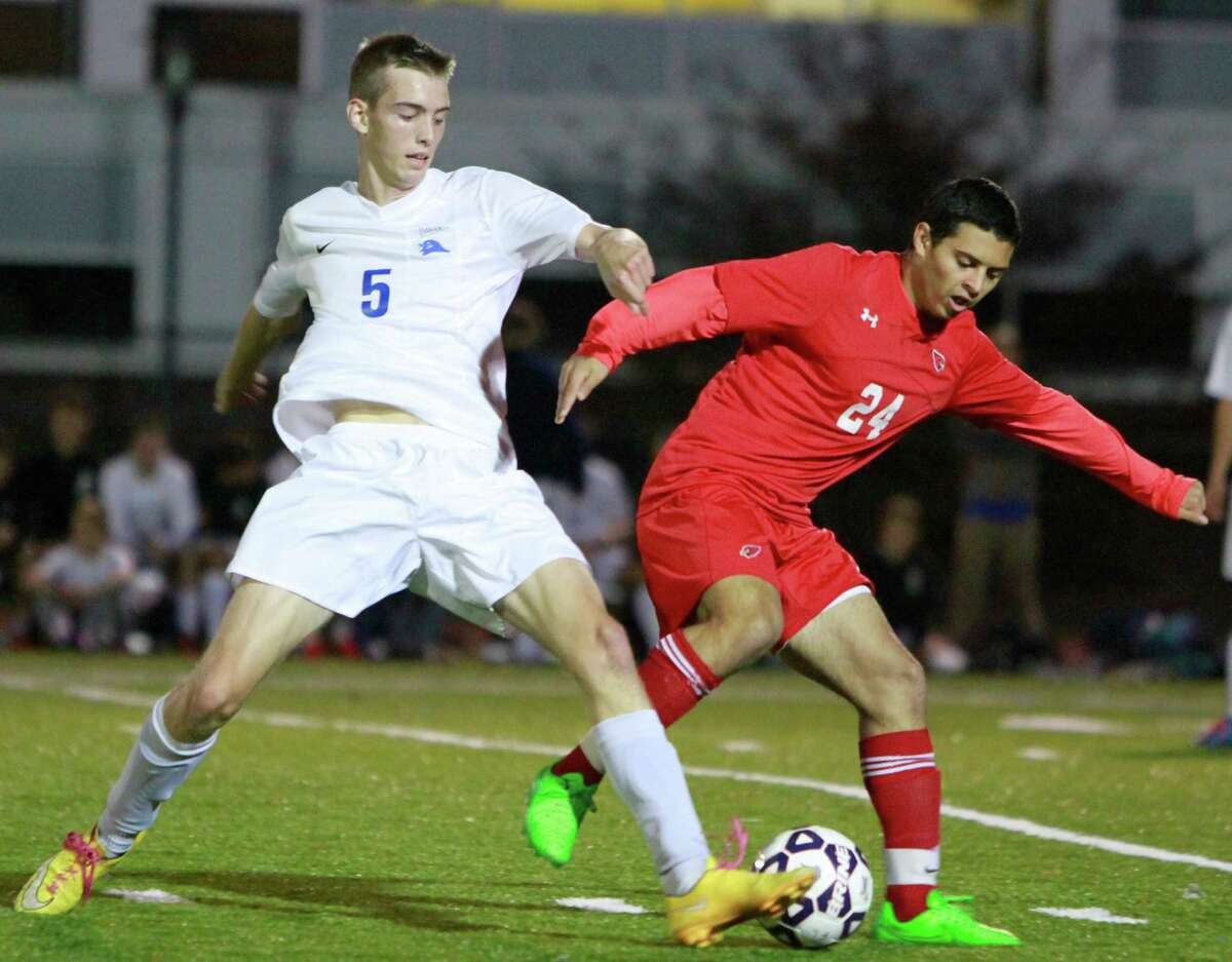 Darien's Sam Pfrommer and Greenwich's Noah Vetter battle for the ball midfield during a FCIAC boys soccer semifinal Monday.