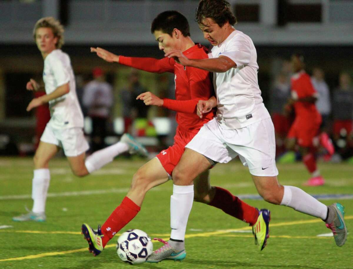 Greenwich's Akira Dunham and Darien's Pablo Martinez battle for the ball during a FCIAC boys soccer semifinal game on Monday in Fairfield. Darien defeated Greenwich 1-0.