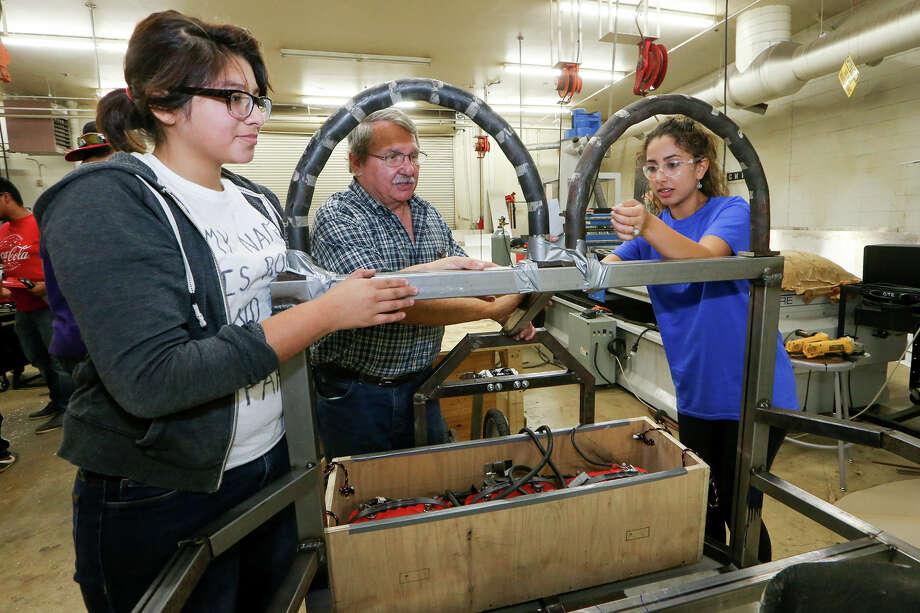 Frances Trejo (left), 16, and Natalie Sahagun, 17, temporarily mount a roll bar with project advisor Bob Franz on a solar powered car being built at Southwest High School on Thursday, July 9, 2015.  The students are building the car in preparation for the upcoming Solar Car Challenge at the Texas Motor Speedway on July 17-23. MARVIN PFEIFFER/ mpfeiffer@express-news.net Photo: Marvin Pfeiffer, Staff / San Antonio Express-News / Express-News 2015
