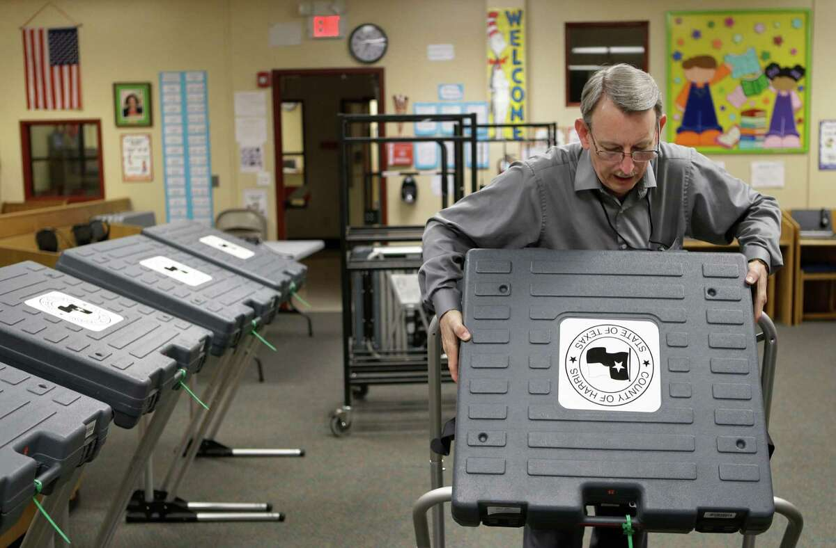 Charles Holloway sets up the polling station at Brookline Elementary on the South Loop for the Nov. 3 election.