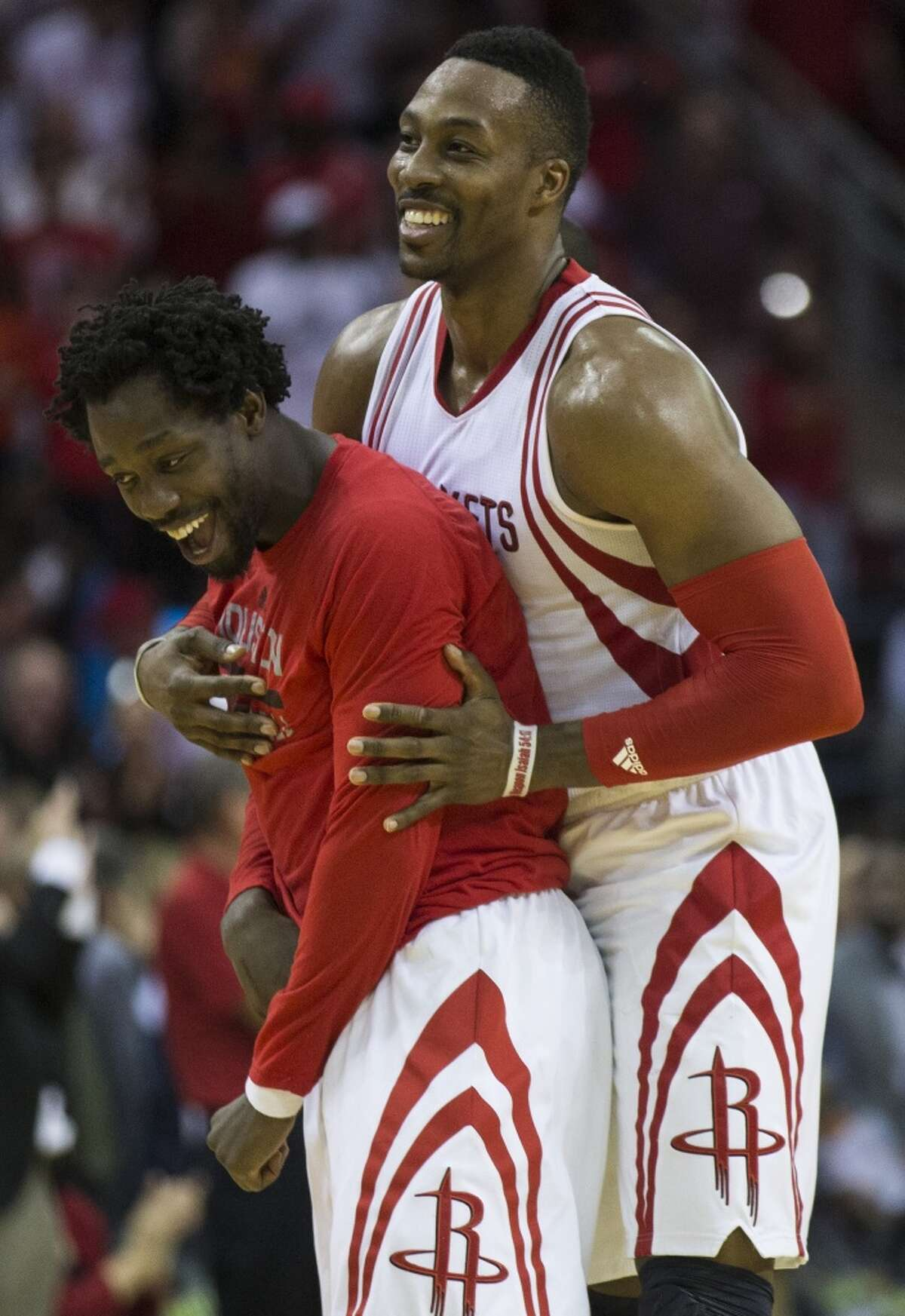Houston Rockets center Dwight Howard (12) and Houston Rockets guard Patrick Beverley (2) embrace after Howard hit a pair of free throws near the end of the fourth quarter as the Rockets beat the Oklahoma City Thunder 110-105 at Toyota Center Monday, Nov. 2, 2015, in Houston. ( Brett Coomer / Houston Chronicle )