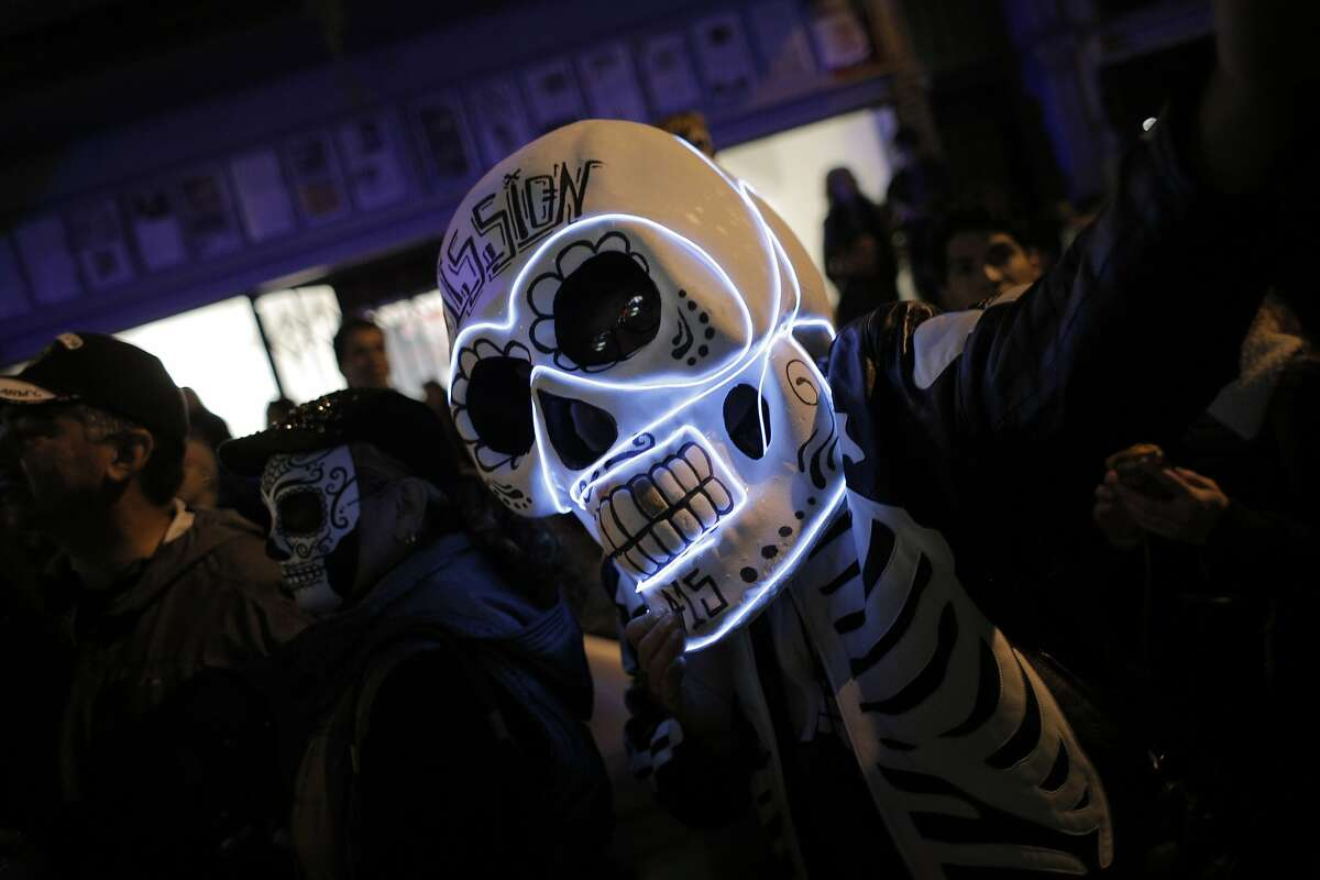 A Day of the Dead celebrant stands on 24th Street during a Day of the Dead celebration in the Mission district in San Francisco, Calif., on Monday, November 2, 2015.