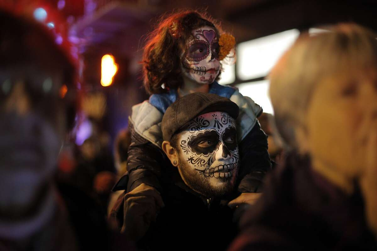Eva Uscanga, 4, sits on her dad Fabricio's shoulders during a Day of the Dead celebration in the Mission district in San Francisco, Calif., on Monday, November 2, 2015.