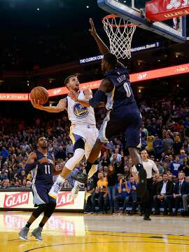 OAKLAND, CA - NOVEMBER 02:  Stephen Curry #30 of the Golden State Warriors goes up for a shot against JaMychal Green #0 and Mike Conley #11 of the Memphis Grizzlies at ORACLE Arena on November 2, 2015 in Oakland, California. NOTE TO USER: User expressly acknowledges and agrees that, by downloading and or using this photograph, User is consenting to the terms and conditions of the Getty Images License Agreement.  (Photo by Ezra Shaw/Getty Images)