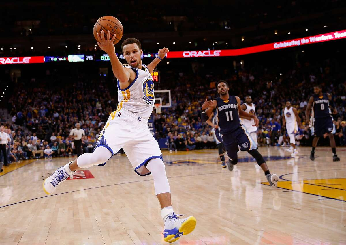 Stephen Curry of the Golden State Warriors saves the ball from going out of bounds then makes a three-point basket over Mike Conley of the Memphis Grizzlies at ORACLE Arena on November 2, 2015 in Oakland, California.