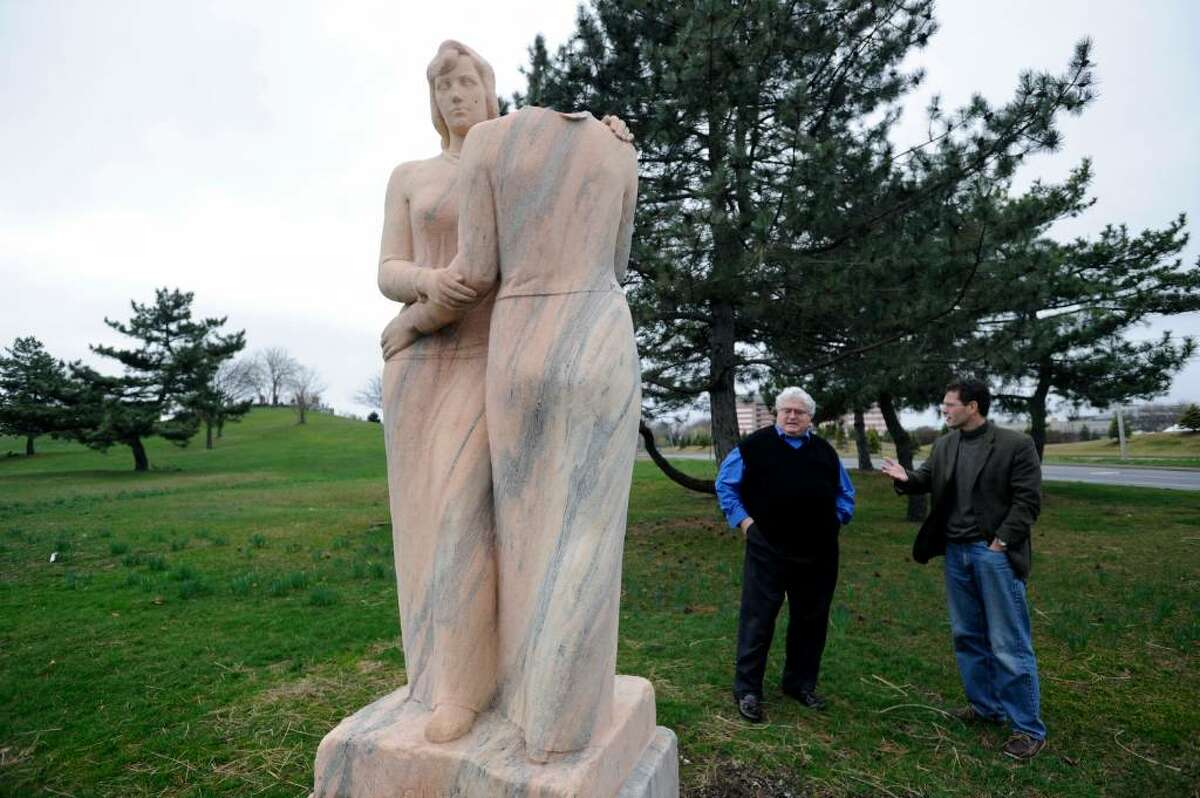 """Shippan residents Ron Malloy, left, and Gauthier Vincent examine the damage done to """"Neighbors,"""" a depression era statue by Henry Kreis,in Czecik Marina Park Sunday afternoon. The statue was damaged when the head of one of the women was cut off and taken. The work depicts two women embracing and was funded by the Works Progress Administration, an agency created to generate jobs in the late 1930s."""