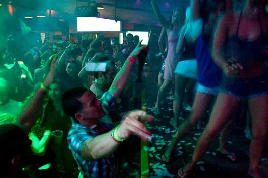 Spring break revelers dance at the Mr. Frogs nightclub in Cancun, Mexico late Thursday, March 18, 2010. Mexico's spring break king, the Caribbean resort of Cancun, is rebounding quickly from last year's triple blow to its tourism industry caused by the country's swine flu epidemic, drug violence and a global economic crisis. (AP Photo/Israel Leal) Photo: Israel Leal, ASSOCIATED PRESS / AP2010