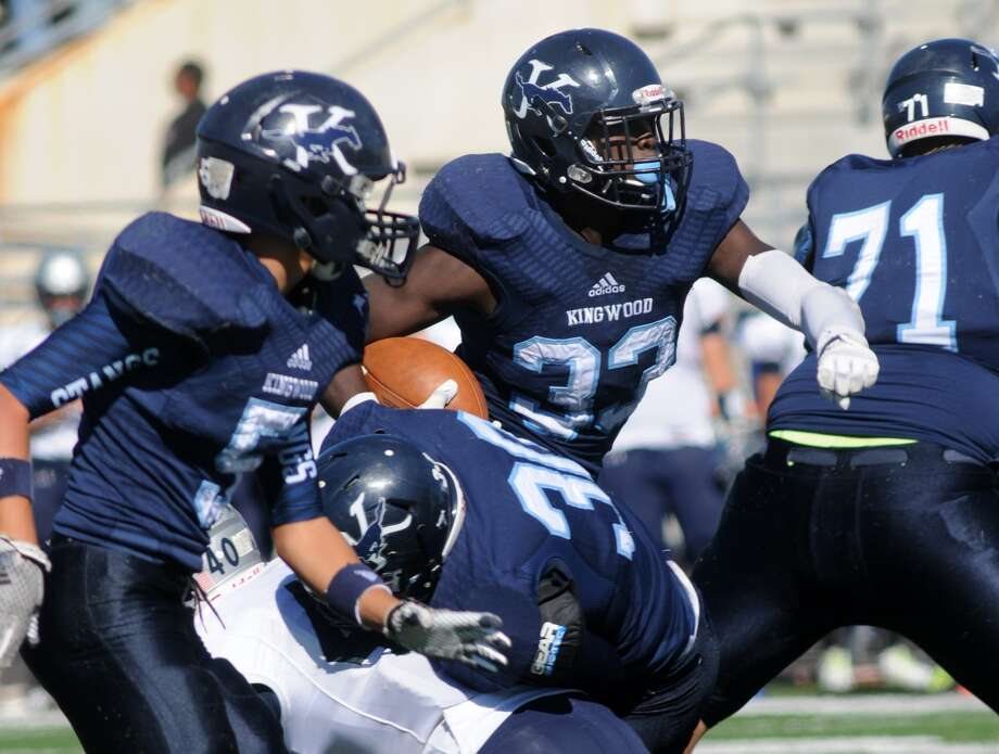 Kingwood junior running back Sewo Olonilua (33) works for yardage between teammates Doug Kent (30) and Luke Vaughters (71) against College Park during their game at Turner Stadium on Nov. 1st. Photo: Jerry Baker, Freelance