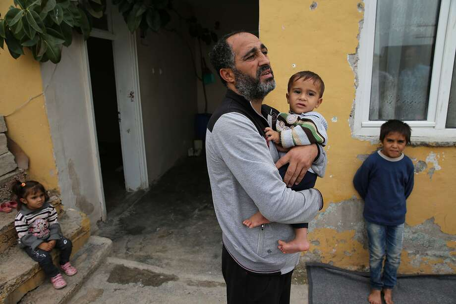 A Syrian refugee family last month stands outside its unfurnished home in Reyhanli, Turkey. The family fled from Palmyra, which was targeted in the Russian air campaign. Photo: Hussein Malla, Associated Press