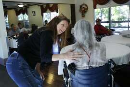 Erin Kane, 50, left, greets her mother Helen Kane, 78, who has Alzheimer's at The Rafael assisted living home Nov. 3, 2015 in San Rafael, Calif. Erin took care of her mother Helen for seven years before she had to move her into an assisted living home earlier this year after it became too difficult for Erin to care for Helen on her own. Erin lives only a few miles from the home and is able to visit her mother multiple times a day.