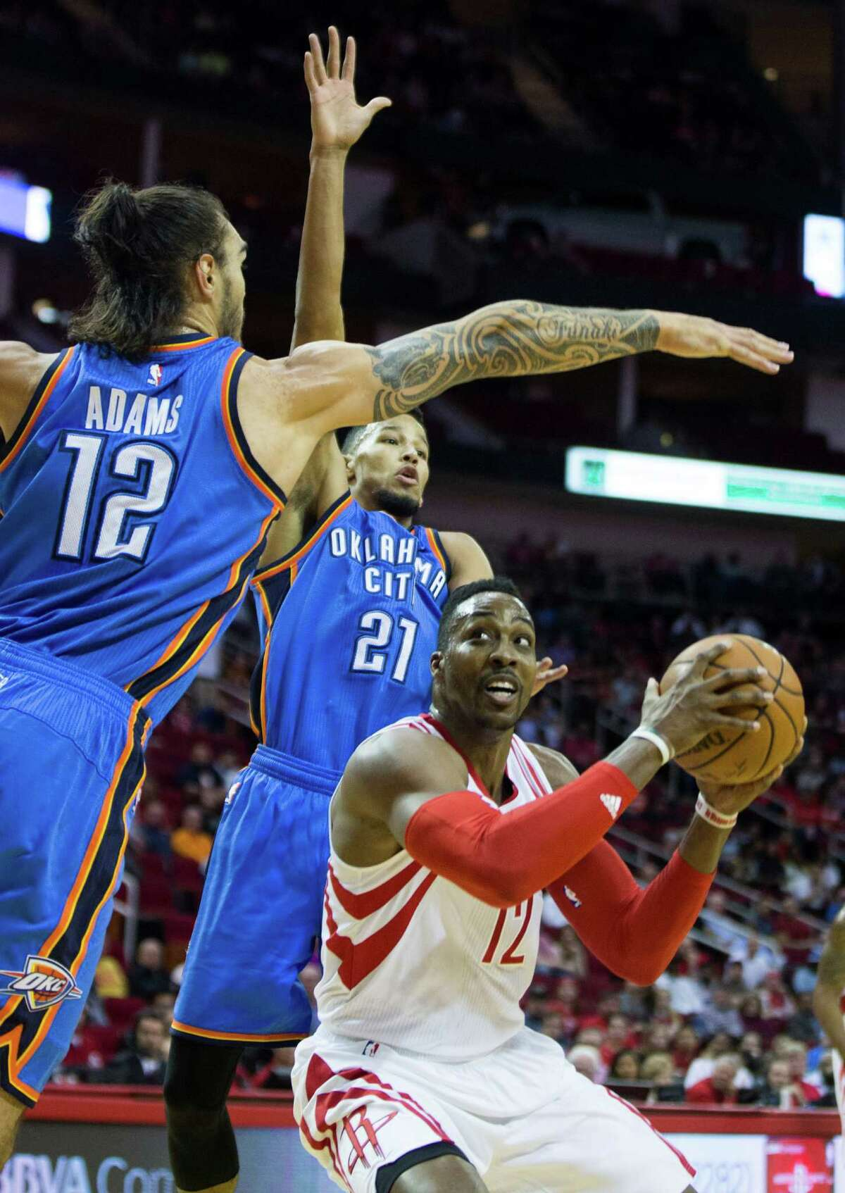 Oklahoma City Thunder center Steven Adams (12) and guard Andre Roberson (21) defend a shot by Houston Rockets center Dwight Howard (12) during the first half of an NBA basketball game at Toyota Center Monday, Nov. 2, 2015, in Houston. ( Brett Coomer / Houston Chronicle )