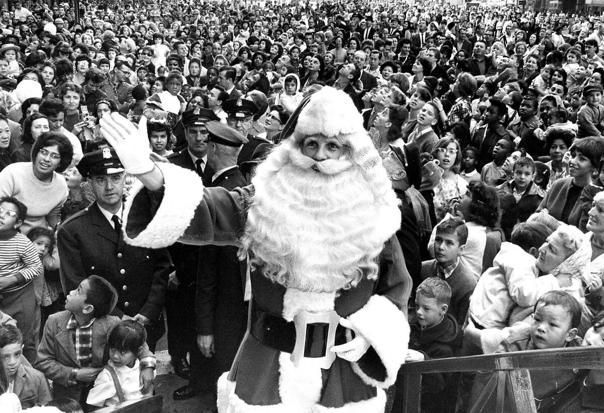 Santa Claus, flanked by huge crowds, arrives at the Emporium on Market Street in 1964.