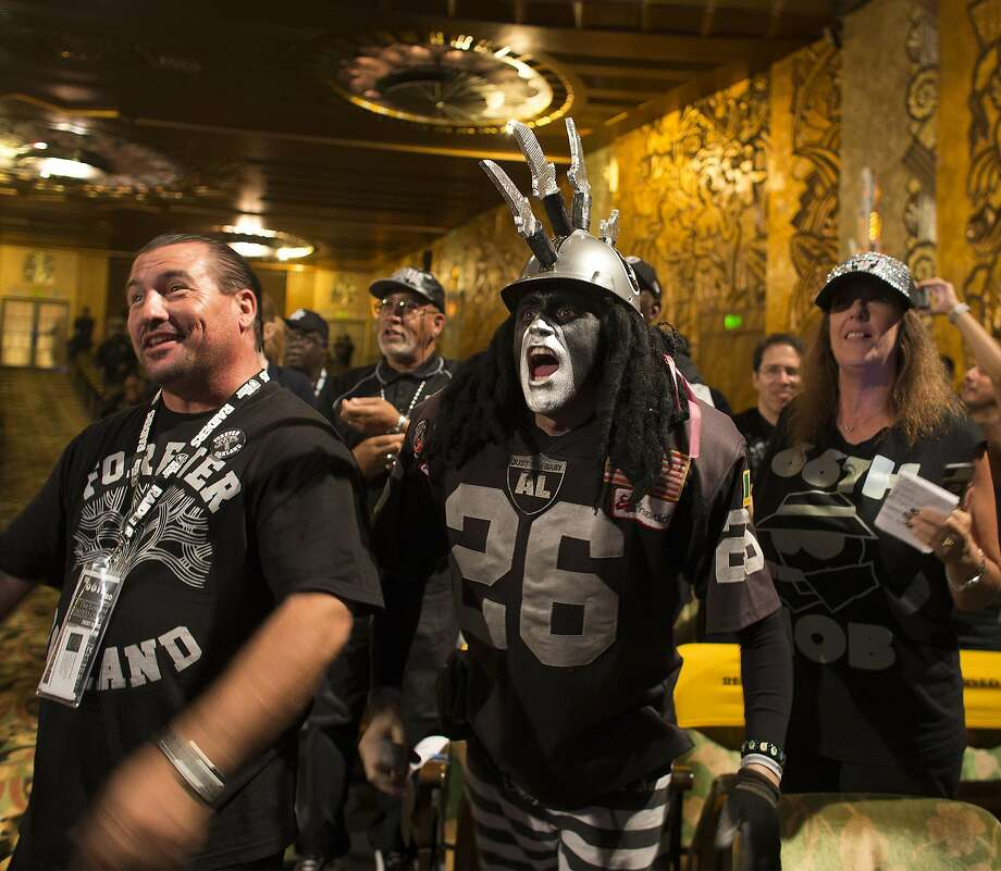 Oakland Raider fan Ray Perez (center) cheers with other fans as Raiders owner Mark Davis speaks during a town hall meeting with NFL executives at the Paramount Theatre. Photo: Gina Ferazzi, McClatchy-Tribune News Service