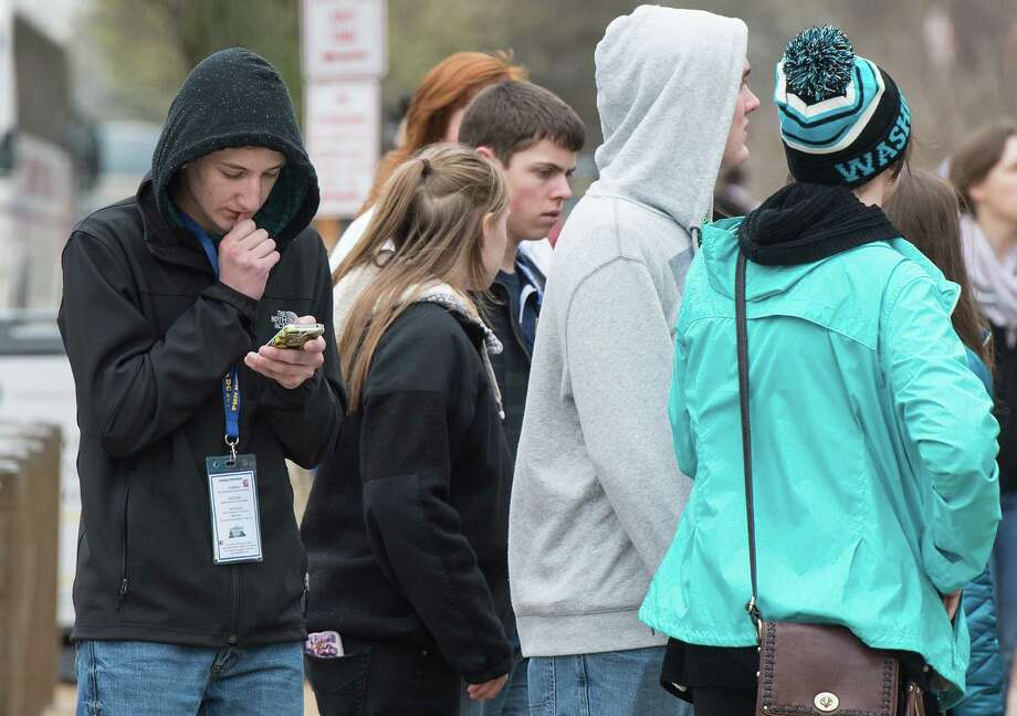 A teenager looks at his smartphone outside the Natural History Museum in Washington, D.C. Photo: Nicholas Kamm /Getty Images / AFP