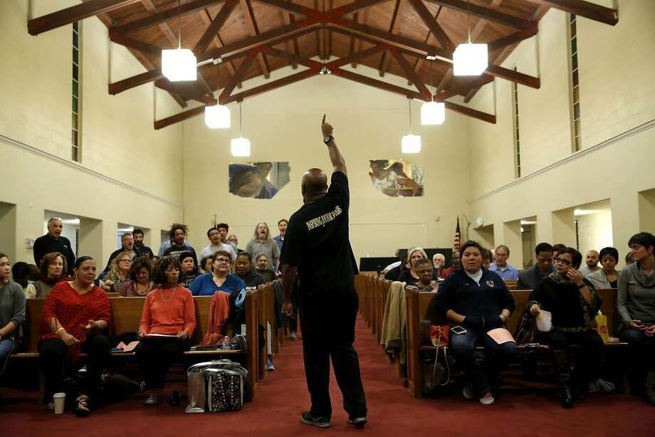Terrance Kelly directs a section of the Oakland Interfaith Gospel Choir during practice at the Imani Community Church in Oakland. Photo: Connor Radnovich, The Chronicle