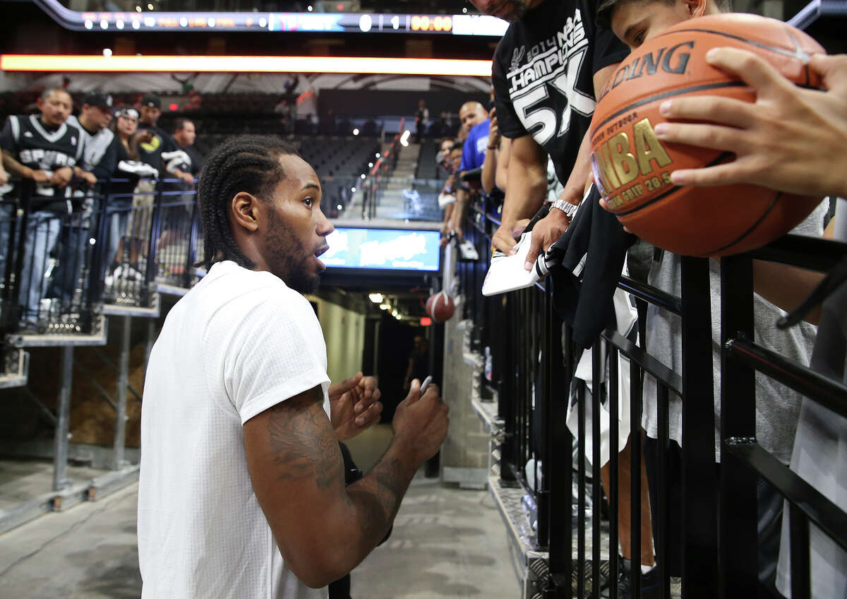 Kawhi Leonard signs autographs pre game as the newly renovated AT&T Center is opened to Spurs fans for the first time on October 18, 2015.
