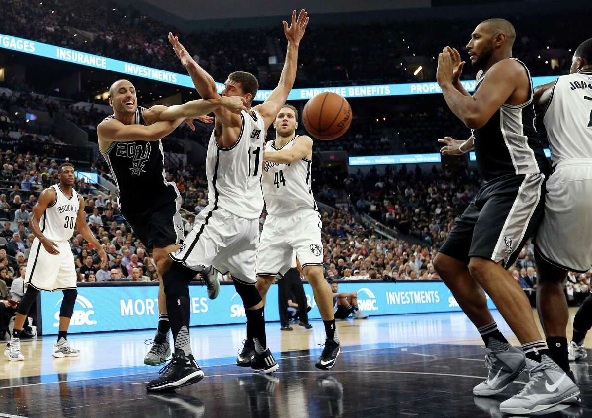 San Antonio Spurs' Manu Ginobili pass to teammate Boris Diaw around Brooklyn Nets' Brook Lopez during first half action Friday Oct. 30, 2015 at the AT&T Center.