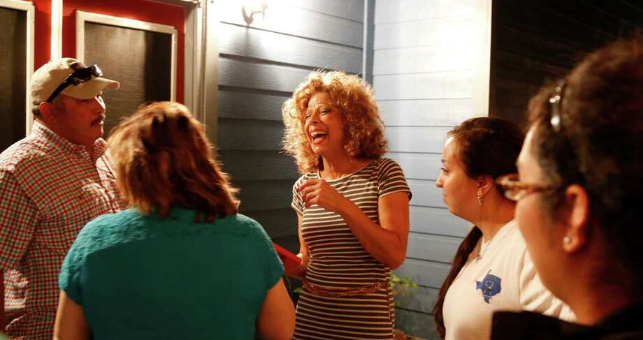 Trina Reyes,C, shares her victory with friends at her home. The town of Von Ormy works to resolve a long-running political rift. Voters will decide on a proposition to change the city from a Type A general law municipality, with a five-member city council and mayor, to Type C municipality with a three-member commission that includes the mayor. Mayor  Reyes, who can remain in office as mayor through May 2017, supports the move to Type C, but has said she may resign if it does not pass. She has consistenly drawn opposition from three city council members over taxation and city services. Photos taken at home of Mayor Trina Reyes on Tuesday, November 3, 2015. Photo: Ron Cortes, Photographer / For The San Anton / Express-News