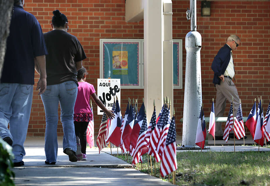 Voters are surrounded by a flag display on their way to vote on Tuesday, November 3, 2015, at Oak Grove Elementary School on Nacogdoches Rd. Photo: Bob Owen, Staff / San Antonio Express-News / ©2015 San Antonio Express-News