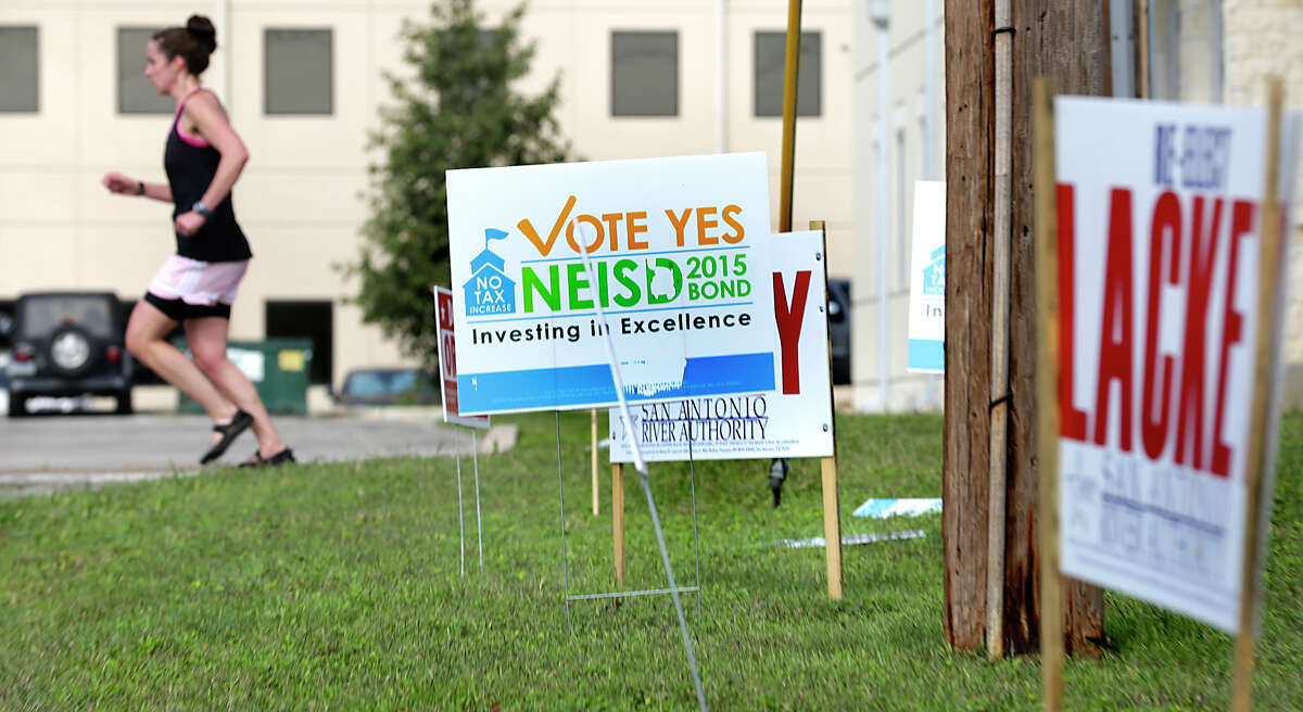 A jogger runs past election polling signs in front of Brook Hollow Library on Heimer Rd. Tuesday, November 3, 2015.