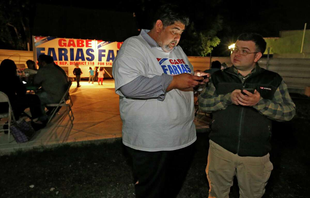 Democrat Gabe Farias (center) and supporter Reid Koenig look for election night results at Farias' campaign party at Southside BBQ. Farias, CEO of the West Side Chamber of Commerce, was among six candidates vying for the District 118 seat.