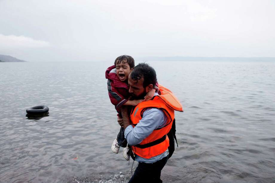 A man carries a young boy after they arrived with other migrants on the shores of the Greek island of Lesbos after crossing the Aegean sea from Turkey on an inflatable dinghy, Wednesday, Sept. 23, 2015. Photo: Petros Giannakouris / Associated Press / AP