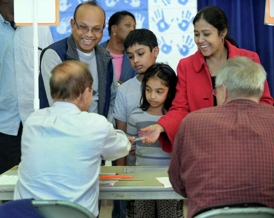 Gazi and Lema Ahmed, with their kids, Rohan,11, and Ritika, 8, check in to vote at the Stadley Rough School polling place in Danbury, Tuesday, Nov. 3, 2015. Photo: Carol Kaliff / Hearst Connecticut Media / The News-Times