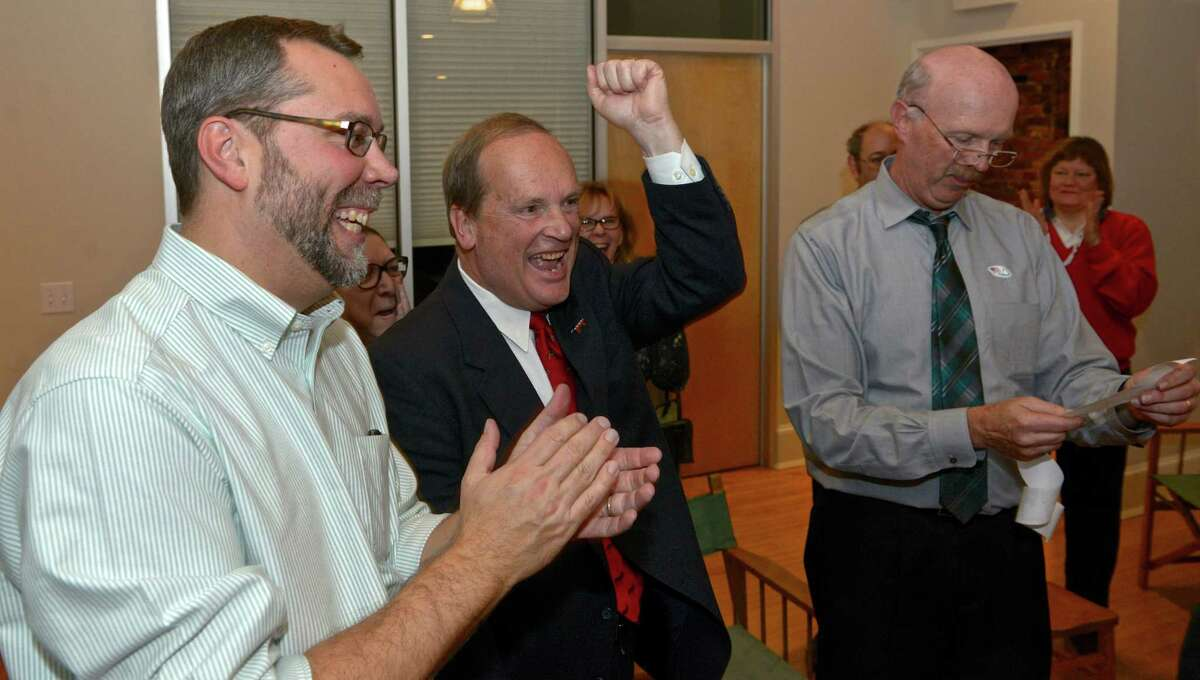 New Milford Democratic candidate for mayor David Gronbach, left, applauds with Scott Chamberlain, town council candidate, as his campaign manager Peter Mullen reads off results from one of the districts Tuesday night.