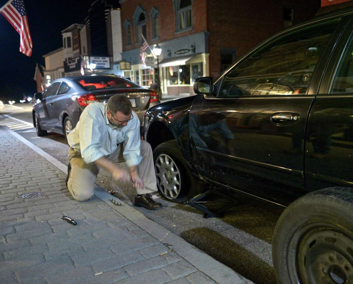 Democratic candidate for mayor David Gronbach changes a flat tire on a supporters car while he waits for the results in the New Milford elections on Tuesday night, November 3, 2015, in New Milford, Conn.