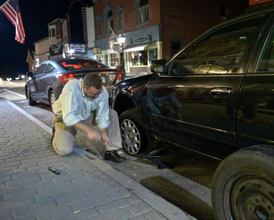 Democratic candidate for mayor David Gronbach changes a flat tire on a supporters car while he waits for the results in the New Milford elections on Tuesday night, November 3, 2015, in New Milford, Conn. Photo: H John Voorhees III / Hearst Connecticut Media / The News-Times