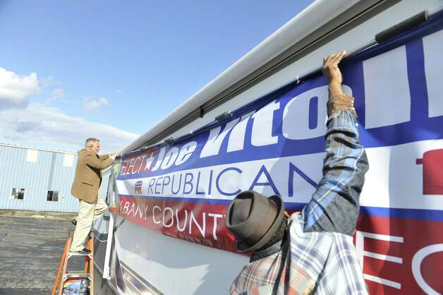 Republican candidate for Albany County Executive, Joseph Vitollo, left, and his friend, Darnell Greene, hang a campaign banner on the side of Vitollo's campaign camper on Thursday, Oct. 29, 2015, in Albany, N.Y.    (Paul Buckowski / Times Union) Photo: PAUL BUCKOWSKI / 00033962A