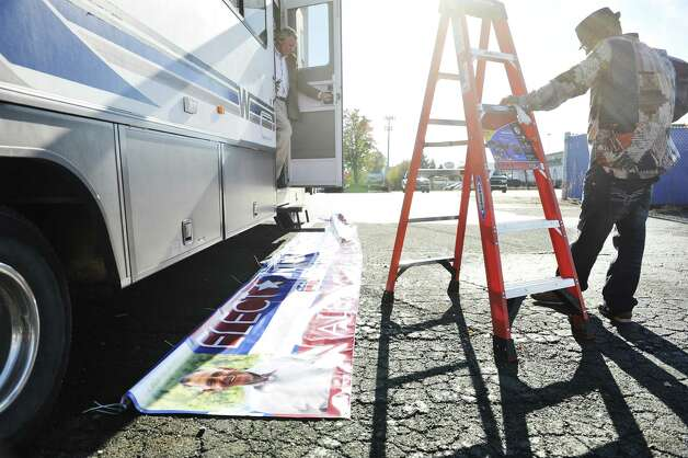 Republican candidate for Albany County executive, Joseph Vitollo, left, and his friend, Darnell Greene, get prepared to hang a campaign banner on the side of Vitollo's campaign camper on Thursday, Oct. 29, 2015, in Albany, N.Y.    (Paul Buckowski / Times Union) Photo: PAUL BUCKOWSKI / 00033962A