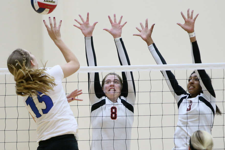 New Braunfels' Lindsey Toney (from left) tries to get a shot past Churchill's Bryncaitlin Walker and Sam Gonzales during their Class 6A bidistrict volleyball playoff match at Alamo Convocation Center on Tuesday, Nov. 3, 2015. New Braunfels beat Churchill in five sets:  20-25, 25-20, 22-25, 25-23, 15-12.   MARVIN PFEIFFER/ mpfeiffer@express-news.net Photo: Marvin Pfeiffer, Staff / San Antonio Express-News / Express-News 2015