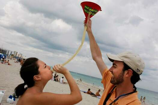 MIAMI BEACH, FL - MARCH 12:  University of Georgia student Casey Schnitzer (L) drinks a beer through a hose as it is held by Matt Bower, a University of Georgia graduate student, during spring break March 12, 2008 on South Beach in Miami Beach, Florida. The traditional break from college began this week.(Photo by Joe Raedle/Getty Images) *** Local Caption *** Casey Schnitzer;Matt BOwer Photo: Joe Raedle, Getty Images / 2008 Getty Images