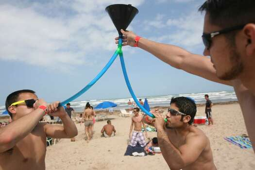 SOUTH PADRE ISLAND, TX - MARCH 25:  Students from the University of Texas El Paso drink from a beer funnel on the beach at South Padre Island, Texas March 25, 2008 during the annual ritual of Spring Break.  The South Texas island is one of the top Spring Break destinations and attracts students from all over the country.  (Photo by Rick Gershon/Getty Images) Photo: Rick Gershon, Getty Images / 2008 Getty Images