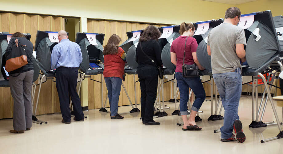 Voters cast ballots at the Metropolitan Multi-Services Center, with the crowd reflecting the high turnout. Photo: Cody Duty, Staff / © 2015 Houston Chronicle