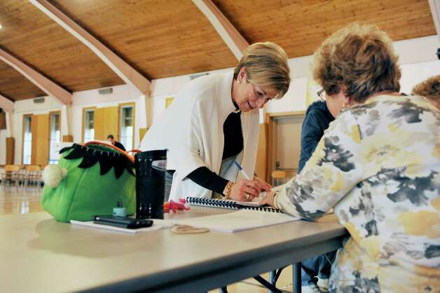 Colonie Town Supervisor candidate, Christine Benedict, signs the voter book before voting in the gym at St. Clare's Church on Tuesday, Nov. 3, 2015, in Colonie, N.Y.  (Paul Buckowski / Times Union) Photo: PAUL BUCKOWSKI / 00034056A