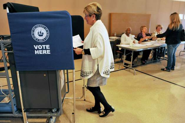 Colonie Town Supervisor candidate, Christine Benedict, places her ballot into the reader as she votes in the gym at St. Clare's Church on Tuesday, Nov. 3, 2015, in Colonie, N.Y.  (Paul Buckowski / Times Union) Photo: PAUL BUCKOWSKI / 00034056A