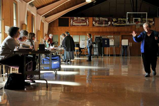 Some voters sign in before casting their votes as other voters leave the gym at St. Clare's Church on Tuesday, Nov. 3, 2015, in Colonie, N.Y.  (Paul Buckowski / Times Union) Photo: PAUL BUCKOWSKI / 00034056A