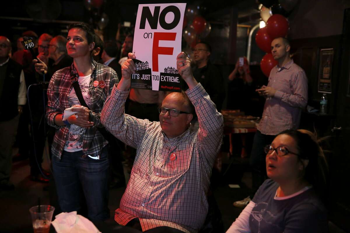 """Bruce Bennett holds a """"No on F"""" sign during an election night party at Oasis in San Francisco, California, on Tuesday, Nov. 3, 2015."""