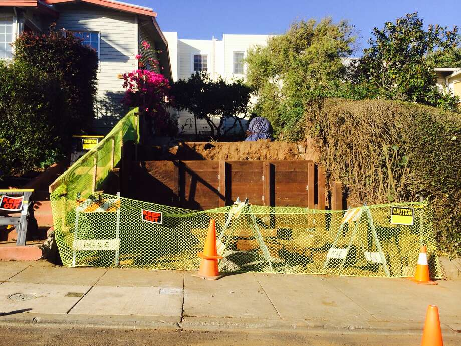 A Sunnyside homeowner dug out his sloped front yard to create a parking space without securing the proper building permit from the city. Now he's added a retaining wall.