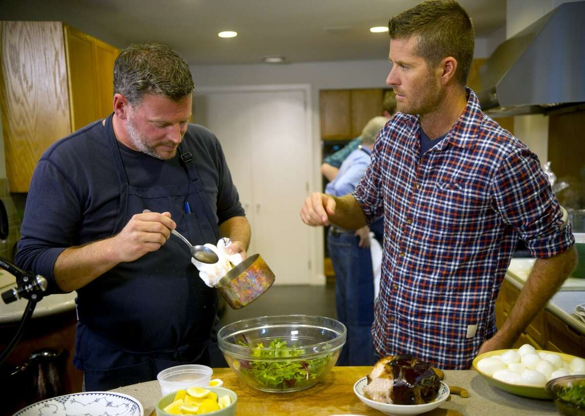 Chef Bill Taibe, left, cooks during a taping of